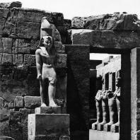 Карнак. Египет. Храм Амона. Вход в храм Рамсеса III из первого двора. На переднем плане статуя этого фараона. Фотограф: Анджей Дзевановский