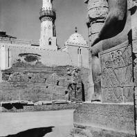 Луксор. Египет. Фрагмент статуи Рамсеса II, стоящей в большом дворе. Вид с западной стороны. В глубине мечеть. Фотограф: Анджей Дзевановский