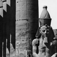 Луксор. Египет. Верхняя часть статуи Аменхотепа III, узурпированной Рамсесом II, на фоне прецессионной колоннады Аменхотепа III. Вид из первого двора. Фотограф: Анджей Дзевановский
