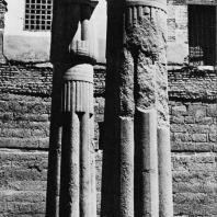 Луксор. Египет. Папирусообразные гранитные колонны более ранней постройки (Среднее царство?), установленные во дворе Рамсеса II. На заднем плане стены мечети. Фотограф: Анджей Дзевановский